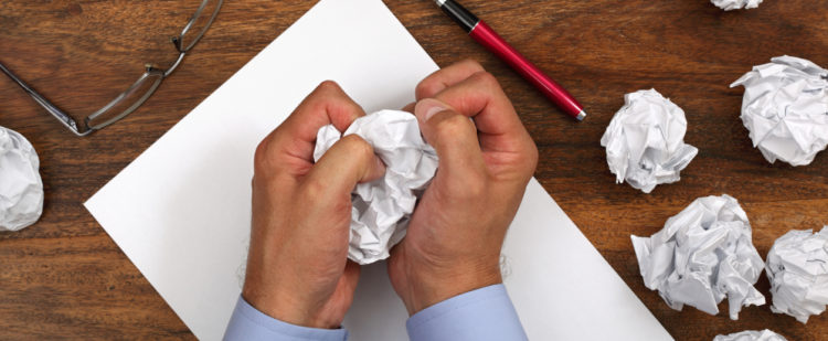 Frustrated man with writers block attempting to write a love note to his wife.
